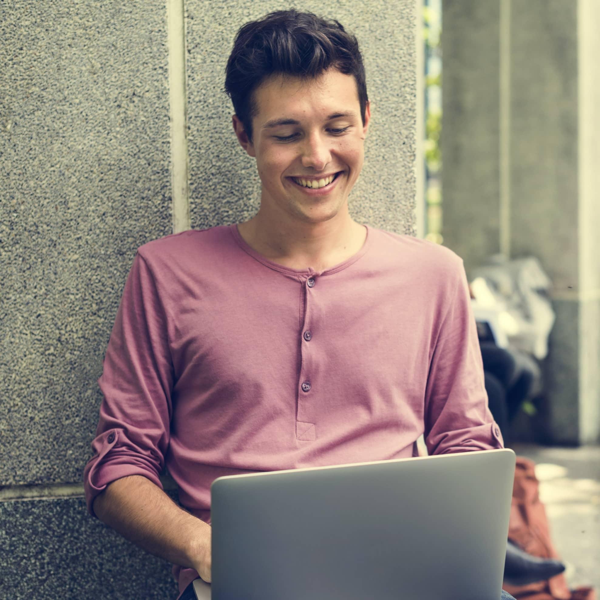 Étudiant qui sourit avec un ordinateur portable